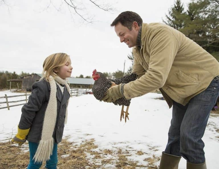 man holding chicken in outside in winter